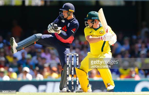 Australia's Aaron Finch plays a shot as England's Jos Buttler looks on during the 2nd oneday international cricket match between England and...