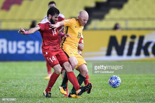 Australia's Aaron Mooy and Syria's Tamer Hag Mohamad compete for the ball during the 2018 World Cup qualifying football match between Syria and...