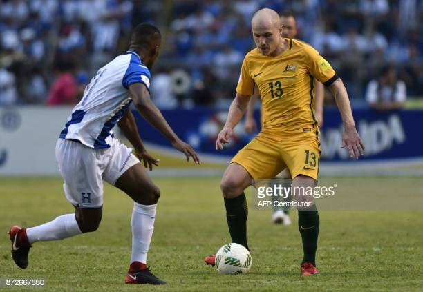 Australia's Aaron Mooy is marked by Honduras' Brayan Beckeles during the first leg football match of their 2018 World Cup qualifying playoff in San...