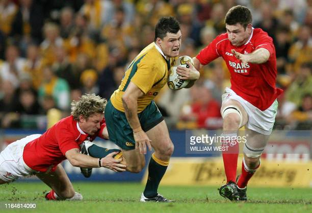 Australia's Adam AshleyCooper breaks through the tackle of Wales centre Jamie Robinson and Michael Owen during their second rugby union Test in...