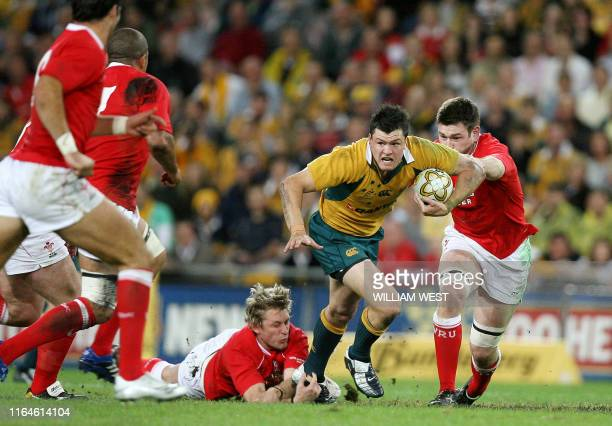 Australia's Adam AshleyCooper breaks through the tackle of Wales centre Jamie Robinson and Michael Owen during their second rugby Test match in...