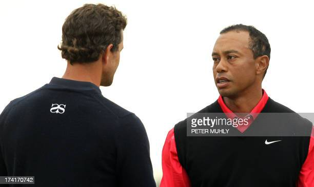 Australia's Adam Scott and US golfer Tiger Woods shake hands at the end of their round on the 18th green during the fourth and final round of the...