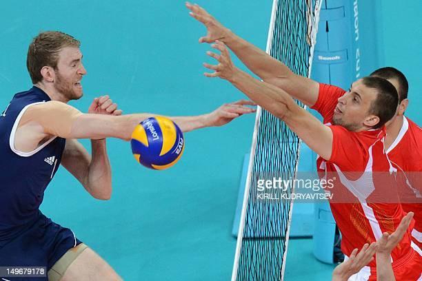Australia's Aidan Zingel spikes as Bulgaria's Viktor Yosifov attempts to block during the Men's preliminary pool A volleyball match between Australia...
