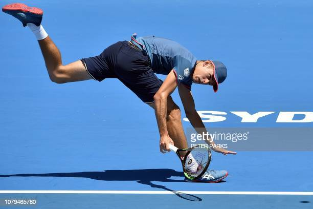 TOPSHOT Australia's Alex De Minaur hits a return against Reilly Opelka of the US during their men's singles second round match at the Sydney...