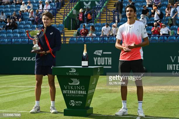 Australia's Alex de Minaur poses with the winner's trophy and Italy's Lorenzo Sonego holds the runner's up trophy after their men's singles finals...