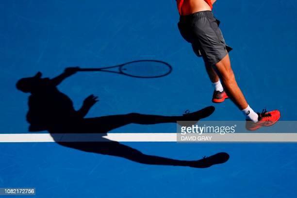 TOPSHOT Australia's Alex de Minaur serves against Portugal's Pedro Sousa during their men's singles match on day one of the Australian Open tennis...