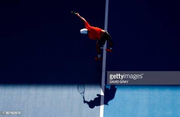 Australia's Alex de Minaur serves to Portugal's Pedro Sousa in their men's singles match on day one of the Australian Open tennis tournament in...