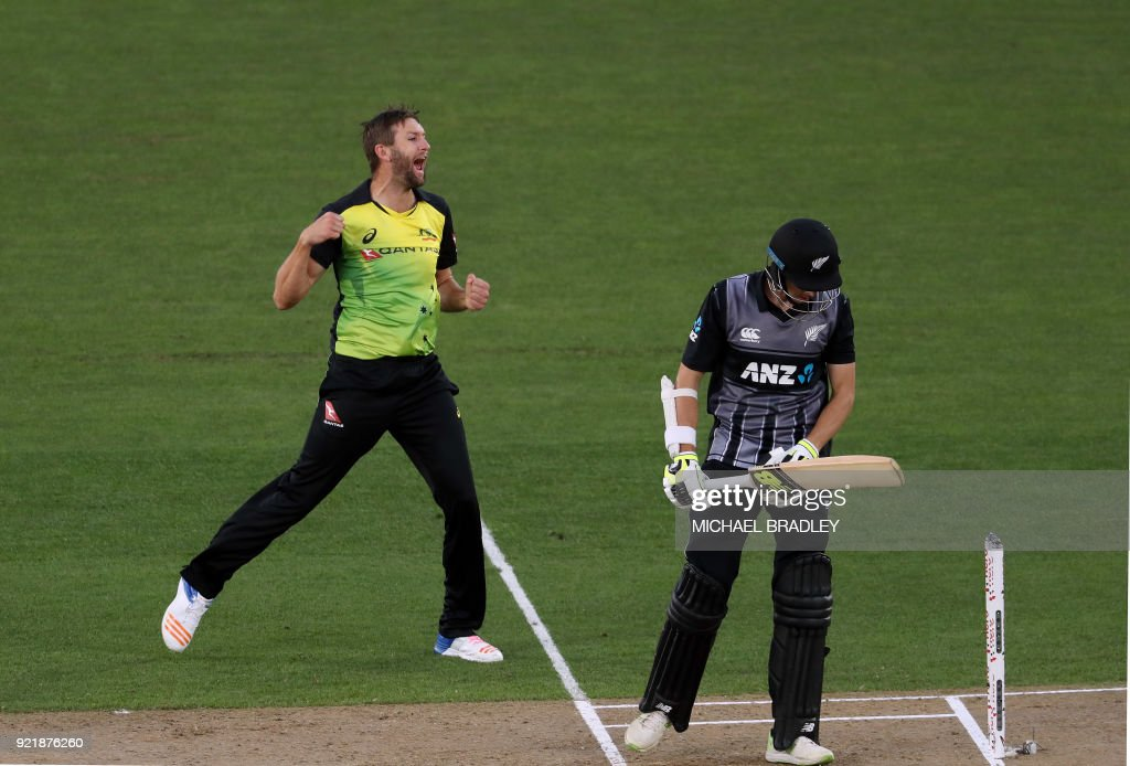 Australia's Andrew Tye (L) celebrates after taking the wicket of New Zealand's Mitchell Santner (R) during the final Twenty20 Tri Series international cricket match between New Zealand and Australia at Eden Park in Auckland on February 21, 2018. /