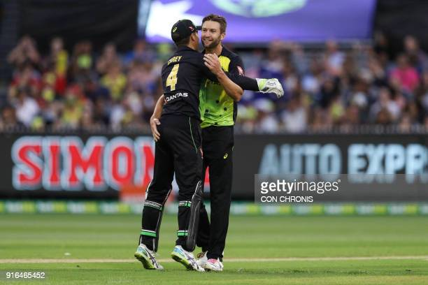 Australia's Andrew Tye celebrates with teammate Alex Carey after bowling out England's Jos Buttler during the Twenty20 International TriSeries...