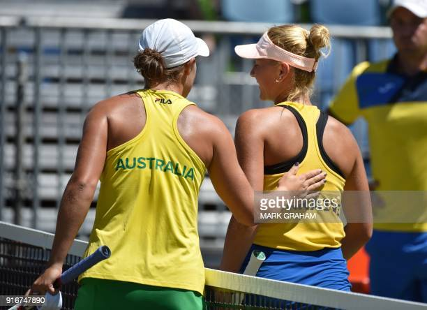 Australia's Ashleigh Barty consoles Ukraine's Marta Kostyuk after her victory in their women's reverse singles Federation Cup tennis match in...