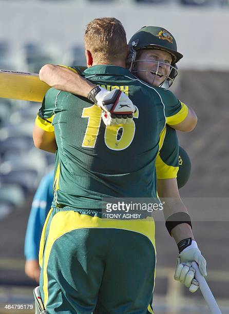 Australia's batsman Aaron Finch celebrates with Steven Smith after scoring a century during the fourth one day international cricket match of the...