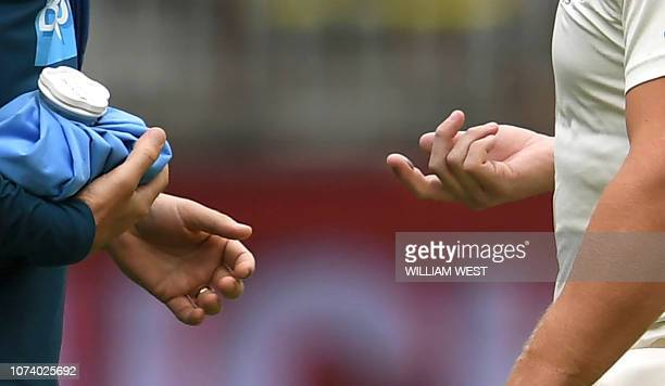 Australia's batsman Aaron Finch has his injured finger inspected after being struck by an Indian delivery on the third day of the second cricket Test...
