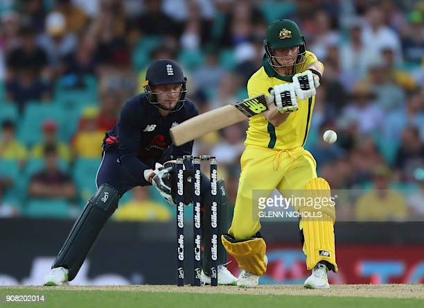 Australia's batsman and captain Steve Smith plays a shot off the England bowling as England's wicketkeeper Jos Buttler looks on during the third...