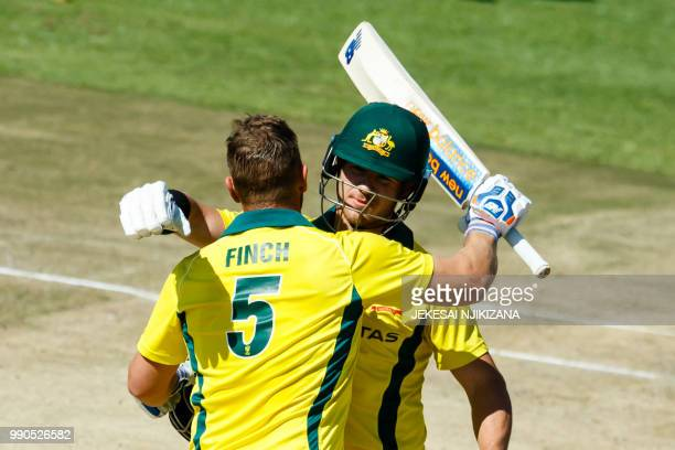 Australia's batsman D'Arcy Short congratulates captain Aaron Finch on reaching a century during the third match played between Australia and hosts...