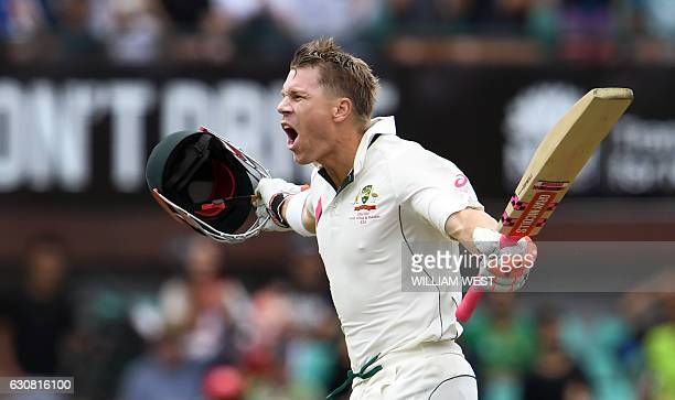 Australia's batsman David Warner celebrates scoring a century against Pakistan during the first day of the third cricket Test match at the SCG in...