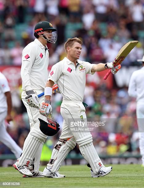 Australia's batsman David Warner celebrates scoring a century against Pakistan next to teammate Matt Renshaw during the first day of the third...