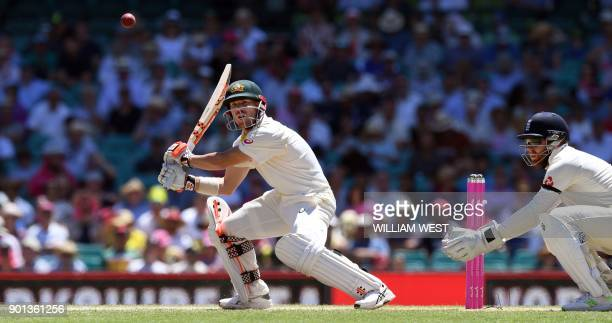 Australia's batsman David Warner cuts a ball as England wicketkeeper Jonny Bairstow looks on during the second day of the fifth Ashes cricket Test...
