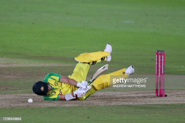 Australia's batsman David Warner falls to the ground after being hit by the ball during the international Twenty20 cricket match between England and...