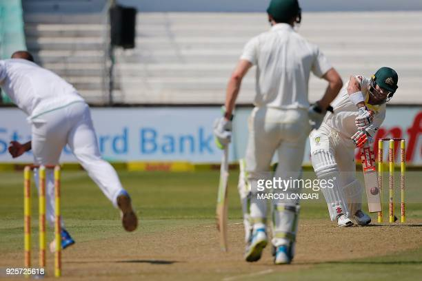 Australia's batsman David Warner hits a four from a ball delivered by South Africa bowler Vernon Philander during day one of the first Sunfoil Test...
