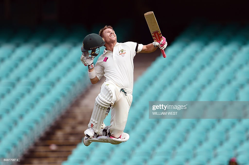 TOPSHOT - Australia's batsman David Warner leaps in the air after scoring his century against the West Indies on the final day of the third cricket Test match in Sydney on January 7, 2016. AFP PHOTO / William WEST WEST