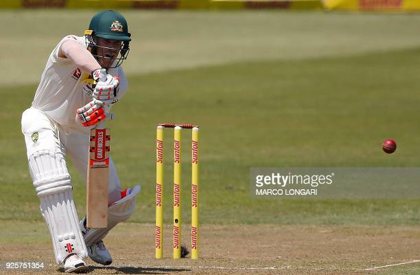 Australia's batsman David Warner plays a shot off a delivery by South Africa's bowler Kagiso Rabada during day one of the first Sunfoil Test between...