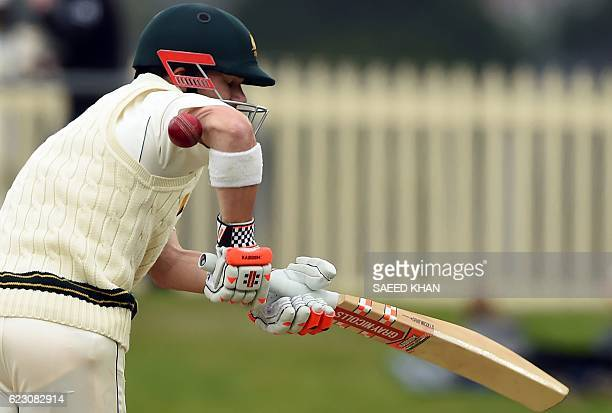 Australia's batsman David Warner reacts as the ball deflects from his hand to the stumps on the third day's play of the second Test cricket match...