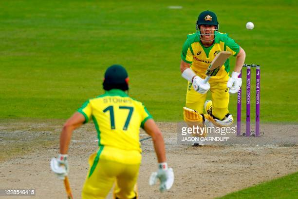 Australia's batsman David Warner shouts to his batting partner Marcus Stoinis during the one-day international cricket match between England and...