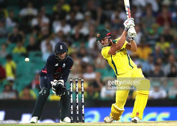 Australia's batsman Marcus Stoinis plays a shot as England's wicketkeeper Jos Buttler looks on during the third oneday international cricket match...
