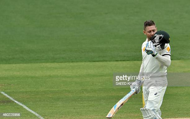 Australia's batsman Michael Clarke kisses his helmet as he celebrates his century on the second day of the first Test cricket match between Australia...
