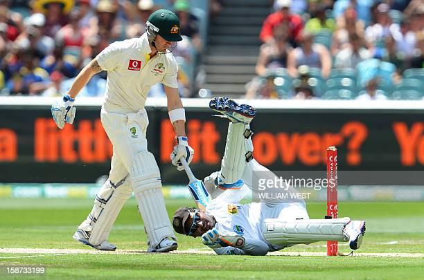 Australia's batsman Michael Clarke looks back to see Sri Lanka's wicketkeeper Kumar Sangakkara miss a stumping opportunity on the second day of the...