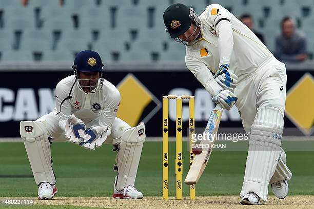 Australia's batsman Michael Clarke plays a shot as India's wicketkeeper Wriddhiman Saha looks on during the second day of the first Test cricket...