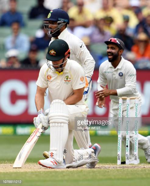 Australia's batsman Mitchell Marsh reacts on his dismissal as India's wicketkeeper Rishabh Pant and a teammate Ajinkya Rahane celebrate during day...