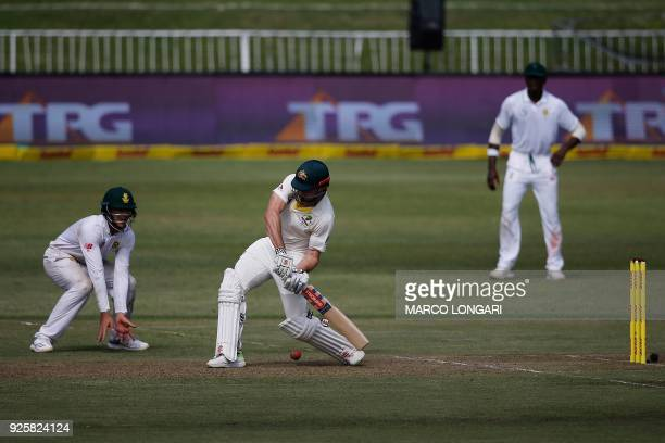 Australia's batsman Shaun Marsh plays a shot off a delivery by South Africa's bowler Keshav Maharaj during day one of the first Sunfoil Test between...