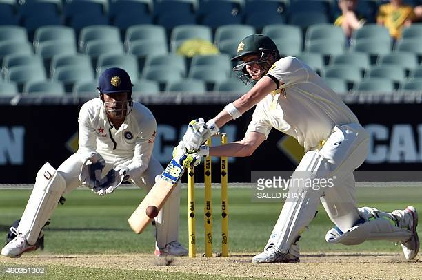 Australia's batsman Steve Smith plays a shot as India's wicketkeeper Wriddhiman Saha looks on the fourth day of the first Test cricket match between...
