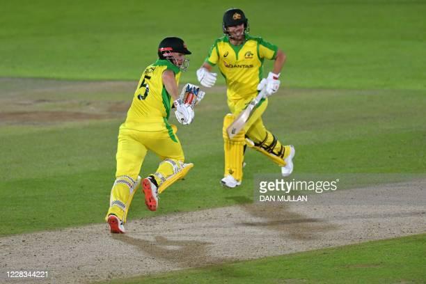 Australia's batsmen David Warner and Aaron Finch run down the wicket during the international Twenty20 cricket match between England and Australia at...