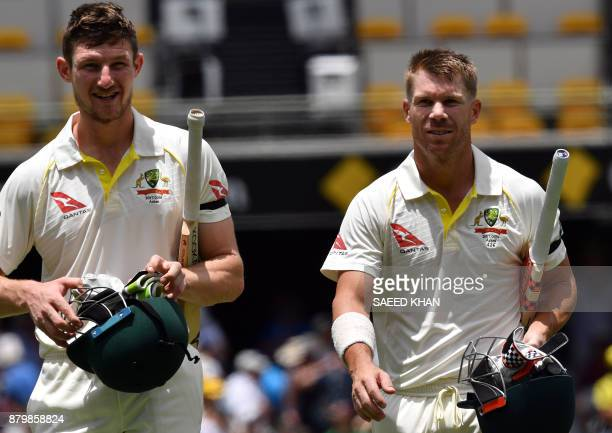 Australia's batsmen David Warner and Cameron Bancroft walk back to the pavilion following their team's victory of the first cricket Ashes Test...