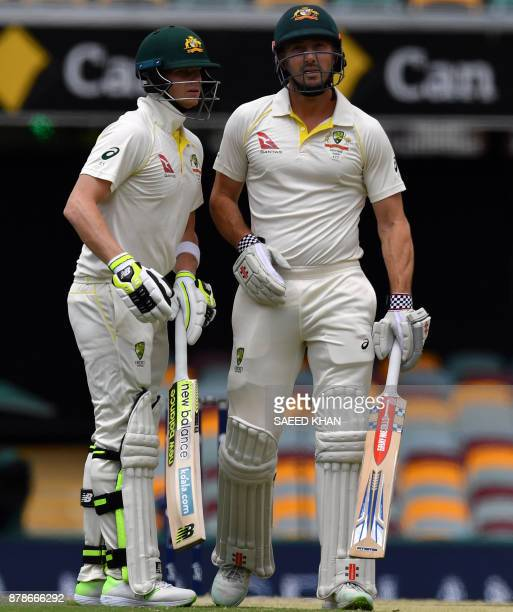 Australia's batsmen Shaun Marsh and Steve Smith talk on the third day of the first cricket Ashes Test between England and Australia in Brisbane on...