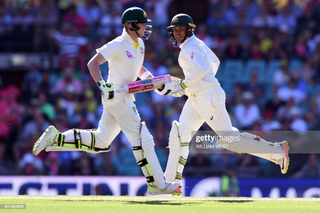 Australia's batsmen Steve Smith (L) and Usman Khawaja take runs from the England bowling on the second day of the fifth Ashes cricket Test match at the SCG in Sydney on January 5, 2018. / AFP PHOTO / William WEST / IMAGE