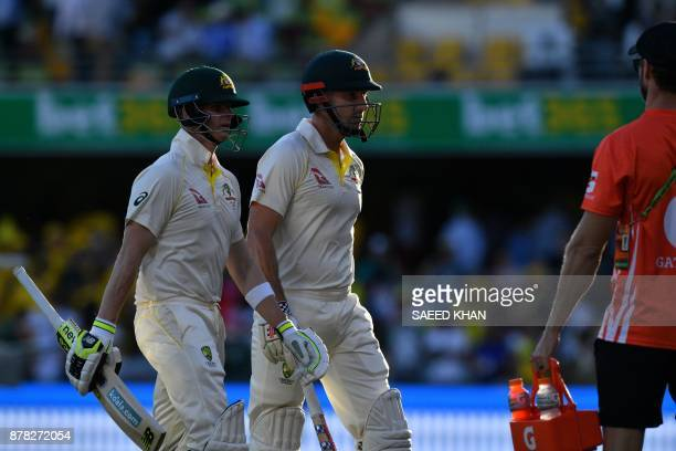 Australia's batting pair Steve Smith and Shaun Marsh walk back to the pavilion at the end of second day of the first cricket Ashes Test between...