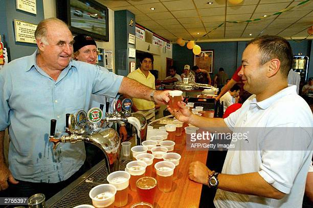 Australia's Bill Young looks on as his father Bill Young Sr hands over a beer to Wallaby coach Eddie Jones at the familyowned Concord Hotel in Sydney...