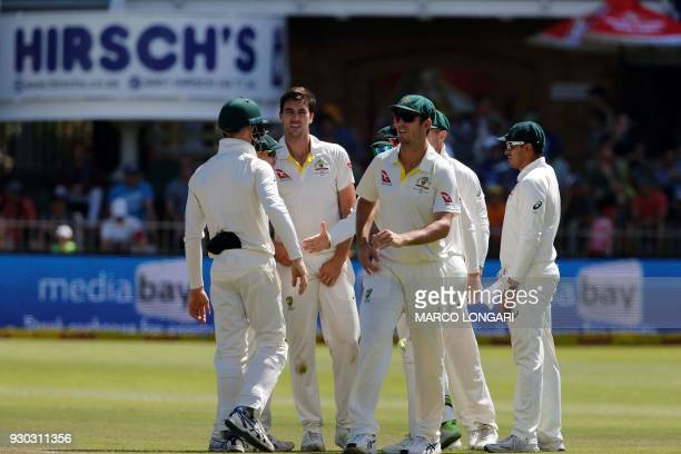 Australia's bowler Pat Cummins celebrates with team mates after taking the wicket of South Africa's batsman Vernon Philander during day three of the...