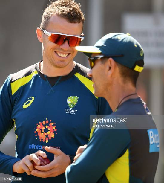 Australia's bowler Peter Siddle talks with coach Justin Langer as they train in the nets in Melbourne on December 25 ahead of the third cricket Test...