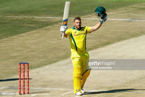 Australia's captain Aaron Finch raises his bat on reaching his century during the third match played between Australia and hosts Zimbabwe as part of...