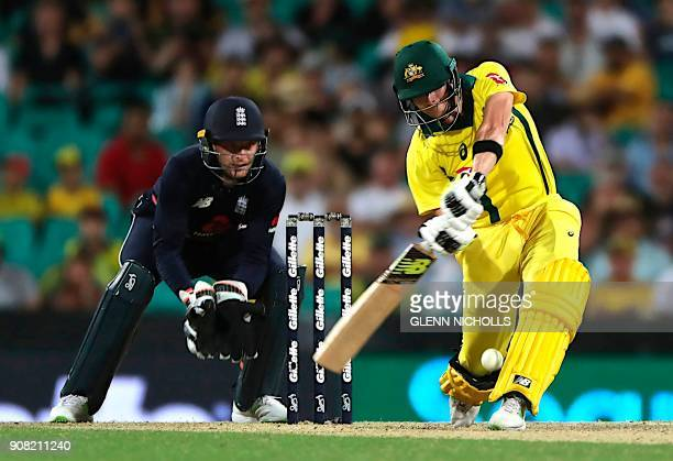 Australia's captain and batsman Steve Smith hits a boundary as England's wicketkeeper Jos Buttler looks on during the third oneday international...