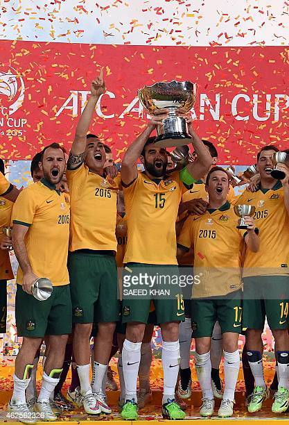 Australia's captain Mile Jedinak holds up the AFC Asian Cup football trophy after beating South Korea at Stadium Australia in Sydney on January 31...