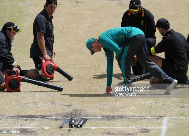 Australia's captain Steve Smith inspects the condition of the wet playing pitch prior to a start on day five of the third Ashes cricket Test match...