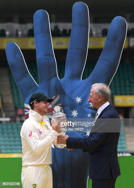 Australia's captain Steve Smith receives a vase from former Australian cricket Bill Lawry after Australia defeated England and retained the Ashes on...