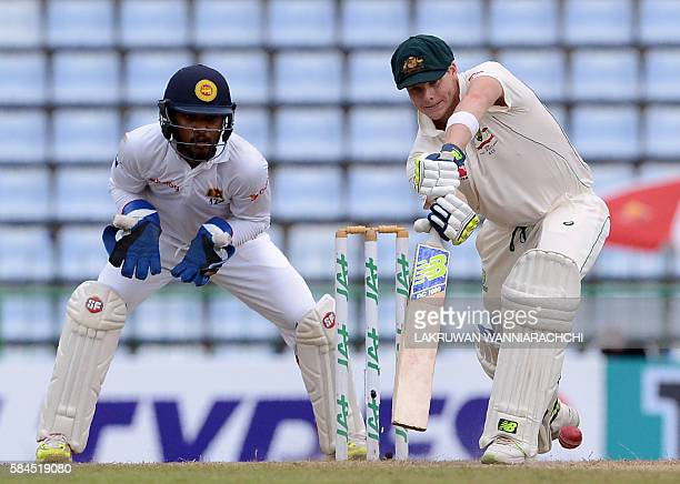 Australia's captain Steven Smith plays a shot as wicketkeeper Dinesh Chandimal looks on during the fourth day of their opening Test match between Sri...