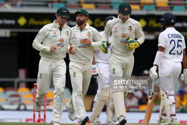 Australia's captain Tim Paine escorts teammates Matthew Wade and Steve Smith to the fielding positions on day two of the fourth cricket Test match...