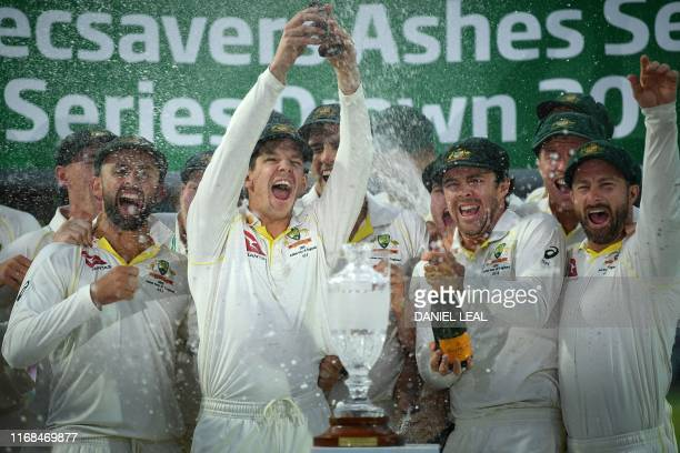 TOPSHOT Australia's captain Tim Paine lifts the Ashes Urn aloft during the presentation ceremony on the fourth day of the fifth Ashes cricket Test...